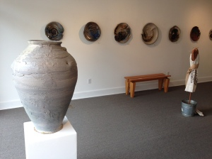 Preston Tolbert, Vessel 2, soda fired stoneware; platters by Preston Tolbert hang on the wall. Copyright (c) the artist.