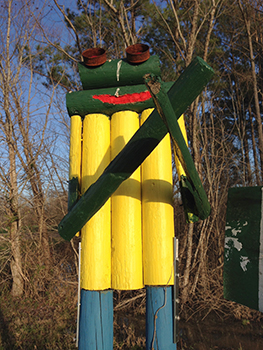 Detail of the frog sculpture beside The Frog Farm sign on Highway 61. Artwork copyright (c) Louise Cadney Coleman.