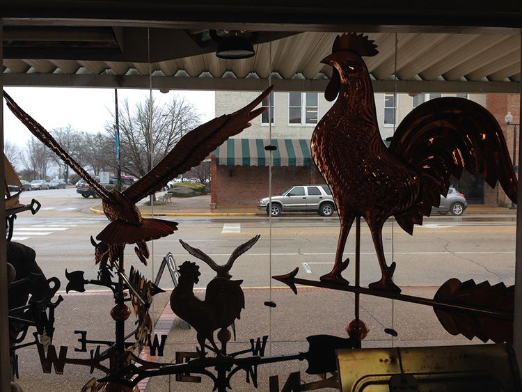 Weather vanes on display in the front window at Tupelo Hardware Company