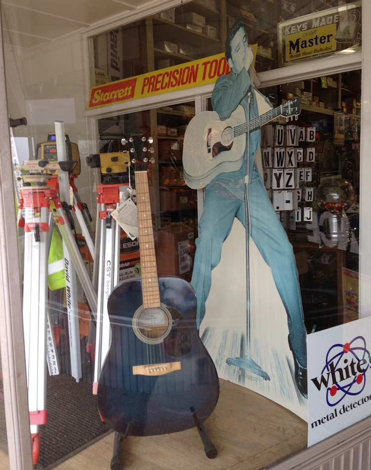 An Elvis Presley cutout, a guitar, and surveying supplies stock another display window at the store.