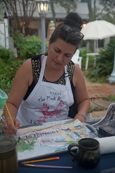 In front of The Pink Rooster art gallery in Ocean Springs, Sherry Phillips Carlson paints a street scene during the Peter Anderson Festival.